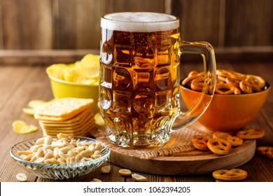 Mug of beer and snacks on wooden background. Selective focus.