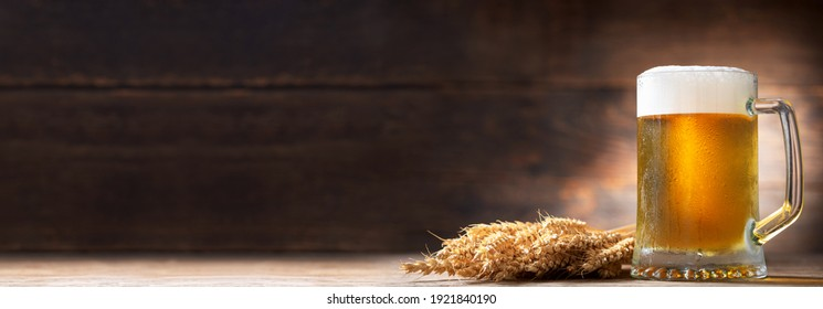 Mug of beer and wheat ears on a wooden background