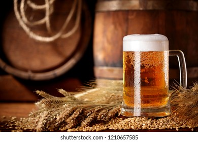 Mug of beer .With wheat and barley and barrels spikes on bakcground.Still life.Copy space