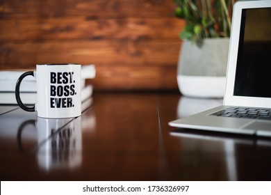 A mug with best boss ever printed on it on different background. Including plant, laptop and books. Isolated subject.