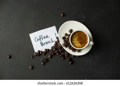 Mug with black coffee, coffee beans, milk and sugar on dark wooden table