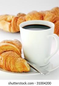 a mug of black coffee with fresh croissants