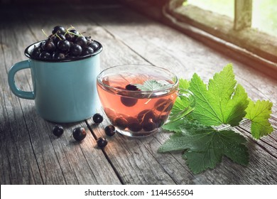 Mug of black currants, glass cup of fruit tea with black currant berries on wooden table inside the retro village house.