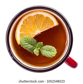 Mug of black tea with lemon and mint top view isolated