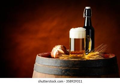 Mug and bottle beer on wooden barrel wit fresh baked bun