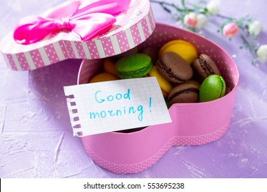Mug cakes Macaron, leaf notebook inscription good morning on purple table top. The cozy breakfast. Copy space.