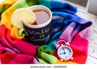 A mug with chalk writing Winter is coming with tea and lemon slice on it, wrapped in a multicolor rainbow scarf with tiny pink alarm clock set to 9 am