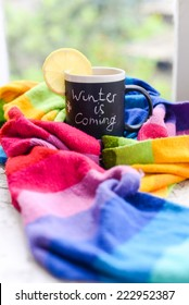 A mug with chalk writing Winter is coming with tea and lemon slice on it, wrapped in a multicolor rainbow scarf