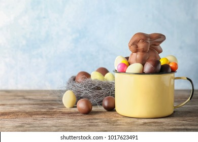 Mug with chocolate Easter bunny and candies on table