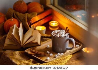 Mug of cocoa or hot chocolate with marshmallows standing next to the window with candles, pumpkins, book and warm blanket. Cozy home atmosphere in rainy autumn day. Нygge lifestyle concept.