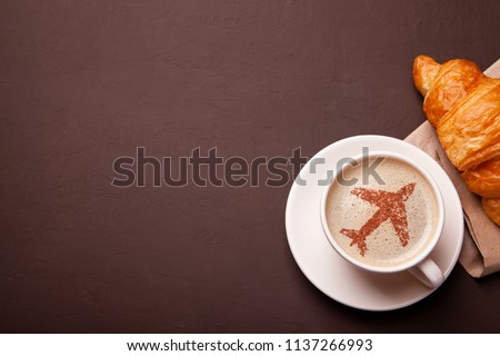 Mug of coffee with an airplane on the foam. Morning coffee with croissant in flight