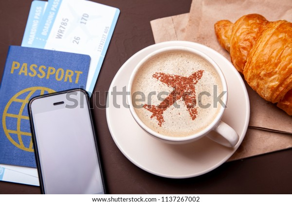 Mug of coffee with an airplane on the foam. Morning coffee with croissant in flight. Paspor and ticket with smrtrfonom and cup of coffee