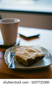 Mug of coffee with cake and polaroid photographs