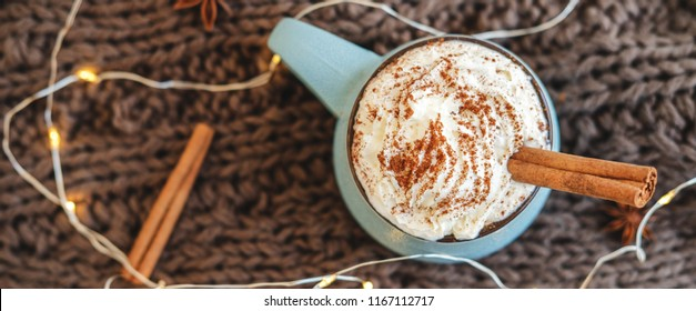Mug of coffee, cocoa or hot chocolate with whipped cream and cinnamon on scarf with garland, anise star. Pumpkin latte - cozy drink for cold autumn or winter. Flat lay. Top view