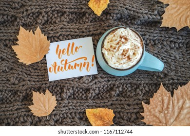 Mug of coffee, cocoa or hot chocolate with whipped cream and cinnamon on scarf with leaves, card Hello Autumn. Pumpkin latte - cozy drink for cold autumn or winter. Flat lay. Top view