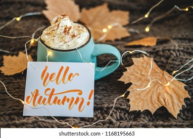 Mug of coffee, cocoa or hot chocolate with whipped cream and cinnamon on scarf with leaves, garland, card Hello Autumn. Pumpkin latte - cozy drink for cold fall or winter