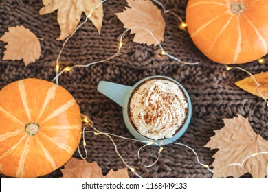 Mug of coffee, cocoa or hot chocolate with whipped cream and cinnamon on scarf with pumpkin, leaves, garland. Pumpkin latte - cozy drink for cold autumn or winter. Flat lay. Top view