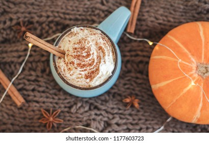 Mug of coffee, cocoa or hot chocolate with whipped cream and cinnamon on scarf with pumpkin, leaves, garland, anise star. Pumpkin latte - cozy drink for cold autumn or winter. Flat lay. Top view