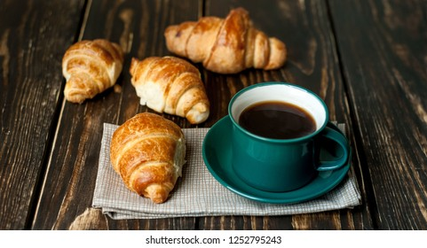mug of coffee, croissants on wooden background