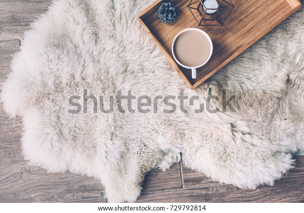 羊の皮の敷物の上に、木製の盆にマグとコーヒーと家庭用デコールを乗せた。冬の週末のコンセプト、平面図
