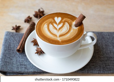 Mug of coffee, latte art or hot chocolate with whipped cream and cinnamon , star anise on wooden background. Top view