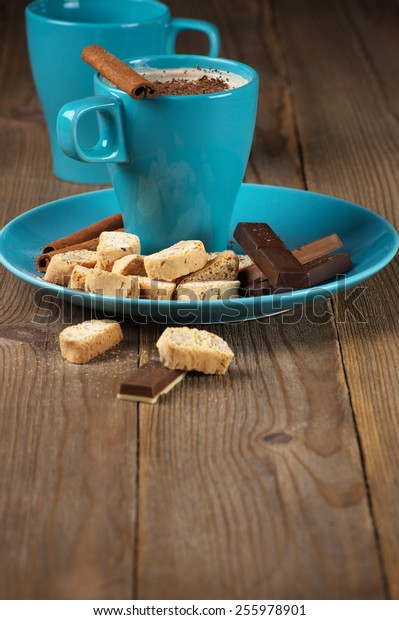 Mug of coffee latte and confectionery on rustic wooden background.