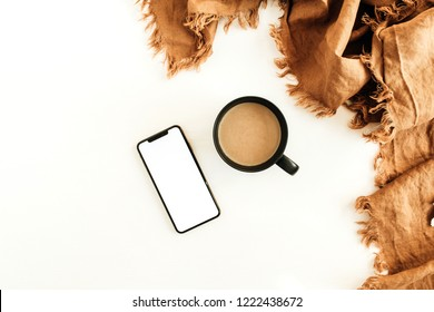 Mug of coffee with milk, ginger blanket, smart phone with blank screen mockup on white background. Flat lay, top view.