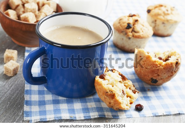 Mug coffee with milk and muffins on the wooden table