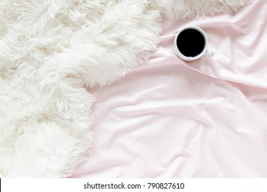 Mug of coffee on a pale pink linens