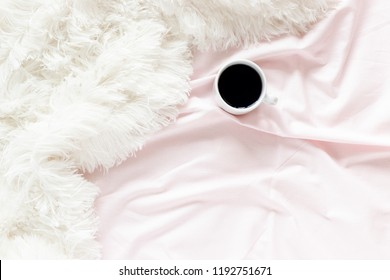 Mug of coffee on a pink linens and white fluffy blanket