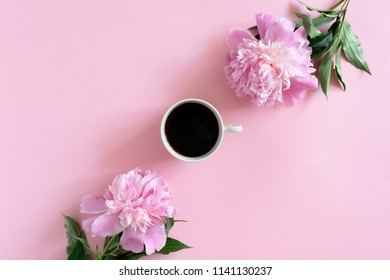Mug of coffee and peonies on a pink pastel background