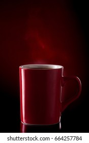 A mug of coffee in a red mug on a red background with smoke, shot in studio.