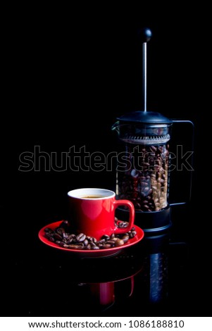A mug of coffee with saucer and a cafetiere