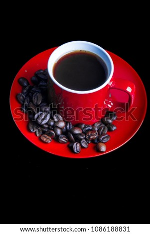 A mug of coffee with saucer and whole roasted coffee beans