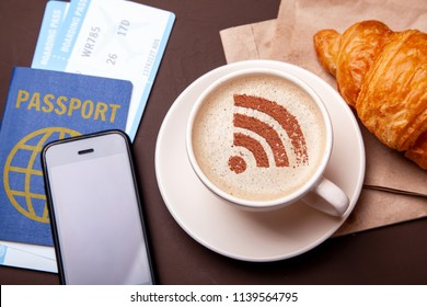 Mug of coffee with WiFi sign on the foam. Free access point to the Internet WiFi. I like coffee break with croissant. Paspor and ticket with smrtrfonom and a cup of coffee