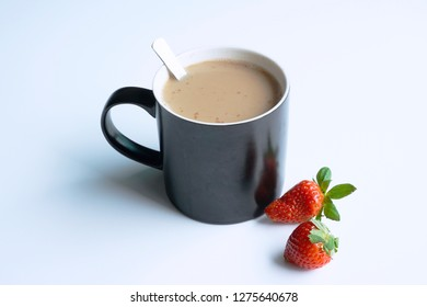 a mug of coffeee and strawberries