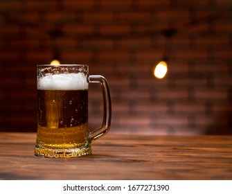 Mug of cold beer with foam on a wooden table in loft interior.