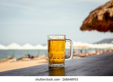 Mug of cold beer with foam on the table. Against the background of the sea. The Restaurant