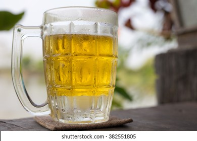 Mug of cold beer with foam on a wooden table outside autumn evening