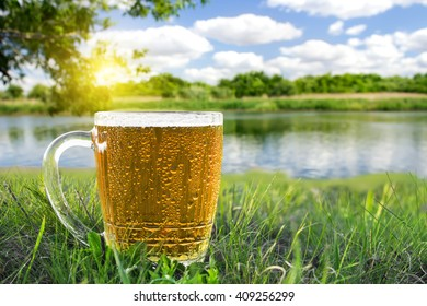 Mug of cold beer on the background of beautiful nature in sunny summer day