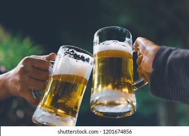 mug of cold craft beer bottoms up, friends drink beer together