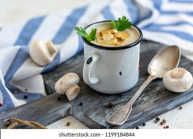 Mug with cream soup, fried mushrooms with onions, parsley, fresh mushrooms and spoon on the serving board, selective focus.