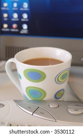 Mug or cup of coffee on office desk with computer keyboard and monitor screen