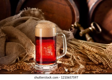 Mug of dark beer .Porter. Still life of dark beer and barrels spikes of wheat and barley on background.Copy space