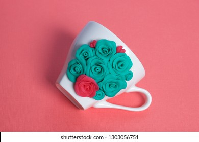 Mug, decorated with flowers made of polymer clay. Crafts from polymer clay. Mug decorated with stucco made of polymer clay