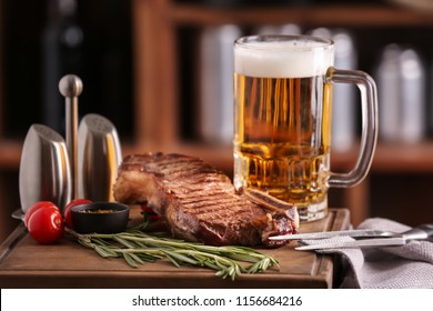 Mug of delicious beer with grilled steak on wooden board