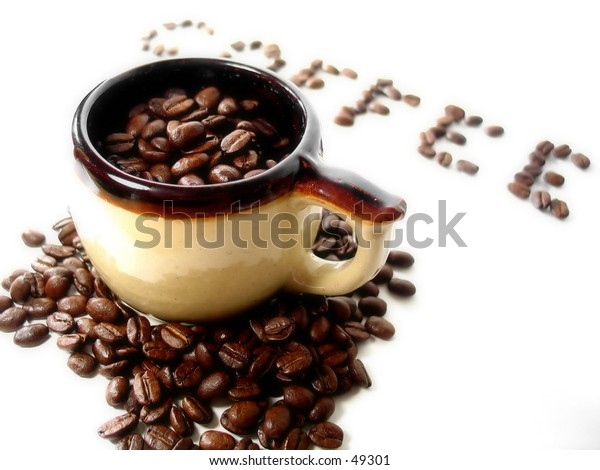 """A mug filled with coffee beans, the word """"coffee"""" spelled out above it, in the distance."""