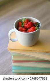 Mug filled with fresh strawberries and stack of book on a table. Selective focus.