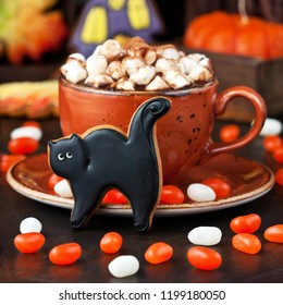 Mug filled with hot chocolate and marshmallows and Halloween gingerbread cookies, tasty Halloween food concept