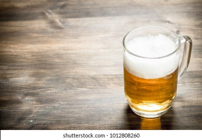 mug of fresh beer. On a wooden table.